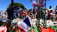 Members of the public lay flowers at a make-shift memorial site on July 15, 2016 in Nice, in tribute to victims of the deadly Bastille Day attack