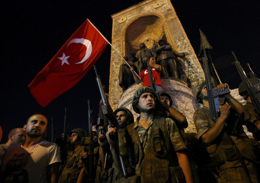 Turkish military stand guard near the the Taksim Square as people wave with Turkish flags in Istanbul, Turkey, July 16, 2016.