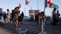 People react near flowers placed on the walkway in tribute to victims, two days after an attack by the driver of a heavy truck who ran into a crowd on Bastille Day killing scores and injuring as many on the Promenade des Anglais, in Nice, France, July 16, 2016.