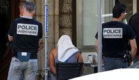 A man covered with a towel is apprehended by French police as the investigation continues two days after an attack by the driver of a heavy truck who ran into a crowd on Bastille Day killing scores and injuring as many on the Promenade des Anglais, in Nice