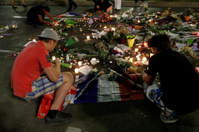 People react near flowers placed on the road in tribute to victims, three days after an attack by the driver of a heavy truck who ran into a crowd on Bastille Day killing scores and injuring as many on the Promenade des Anglais, in Nice, France, July 17, 2016.