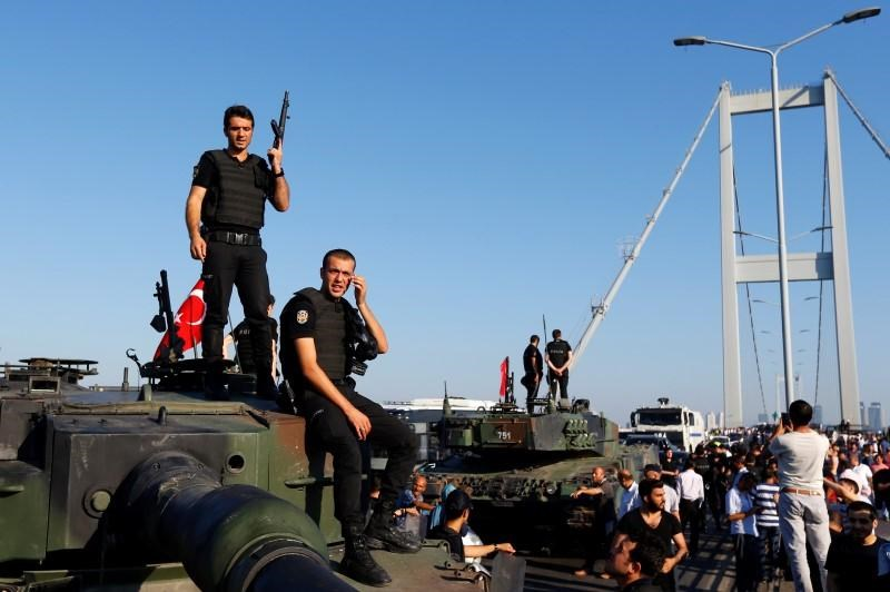 Policemen stand atop military armored vehicles after troops involved in the coup surrendered on the Bosphorus Bridge in Istanbul, Turkey July 16, 2016.