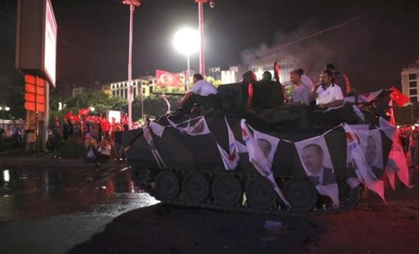 Supporters of Turkish President Tayyip Erdogan sit atop an armored vehicle decorated with Erdogan's portraits in Ankara, Turkey July 16, 2016.