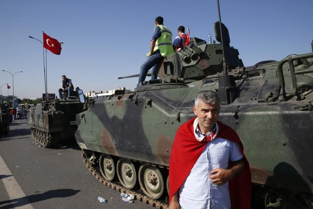 A man wrapped in a Turkish flag stands next to military vehicles in front of Sabiha Airport, in Istanbul, Turkey July 16, 2016.