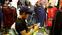 A vendor uses a mobile phone to surf internet at a clothes shop in Paranaque, Metro Manila, Philippines July 7, 2016. Picture taken July 7, 2016.