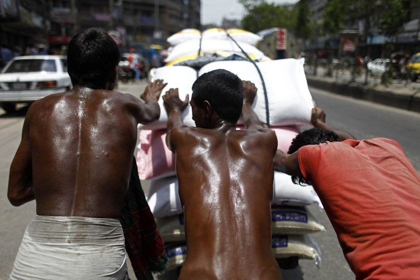 Laborers sweat profusely during the summer heat in Dhaka, Bangladesh. As many as 43 countries, especially those in Asia, including China, Indonesia, and Malaysia, will experience declines in their economies because of heat stress. Photographer: NurPhoto/Corbis via Getty Images