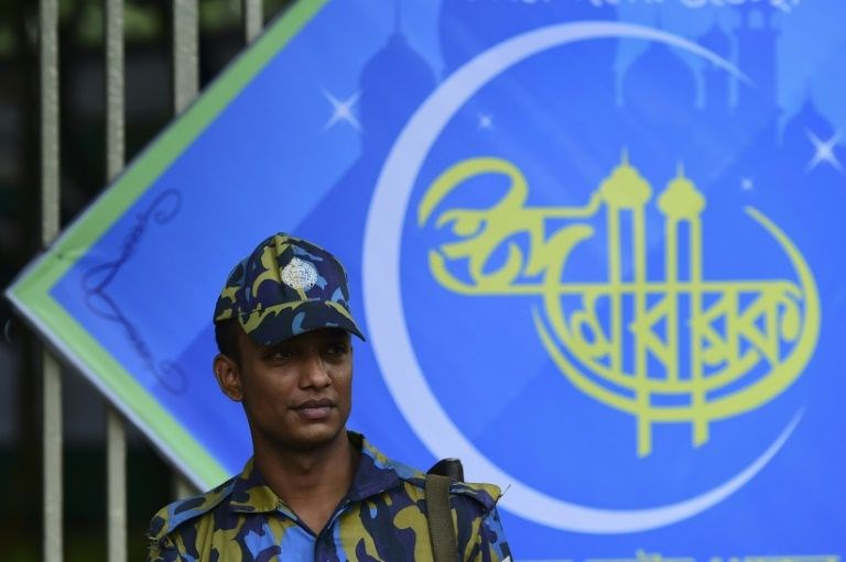 A Bangladeshi policeman stands guard as Muslims offer Eid al-Fitr prayers in Dhaka on July 7, 2016