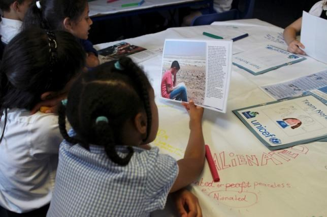 Primary school children, including those with refugee backgrounds, read real-life stories about refugees during a classroom lesson about the refugee crisis at Norbury School in Harrow, London, Britain July 15, 2016. Picture taken July 15, 2016. Thomson Reuters Foundation/Lin Taylor