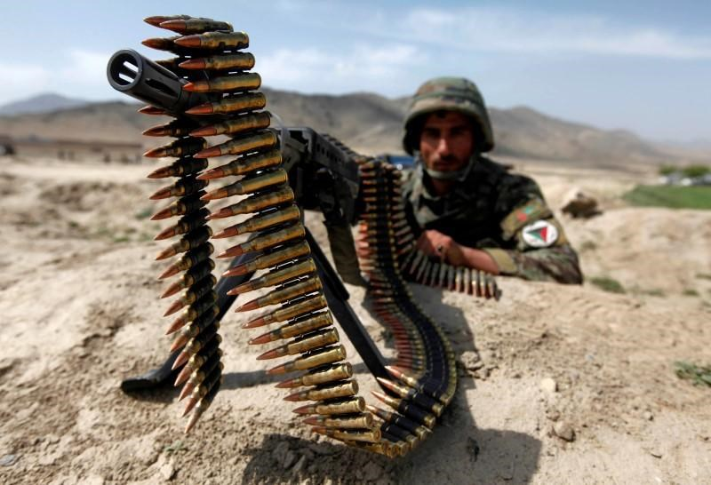 An Afghan National Army soldier holds a position while patrolling the village of But Khak on the outskirts of Kabul May 15, 2012.