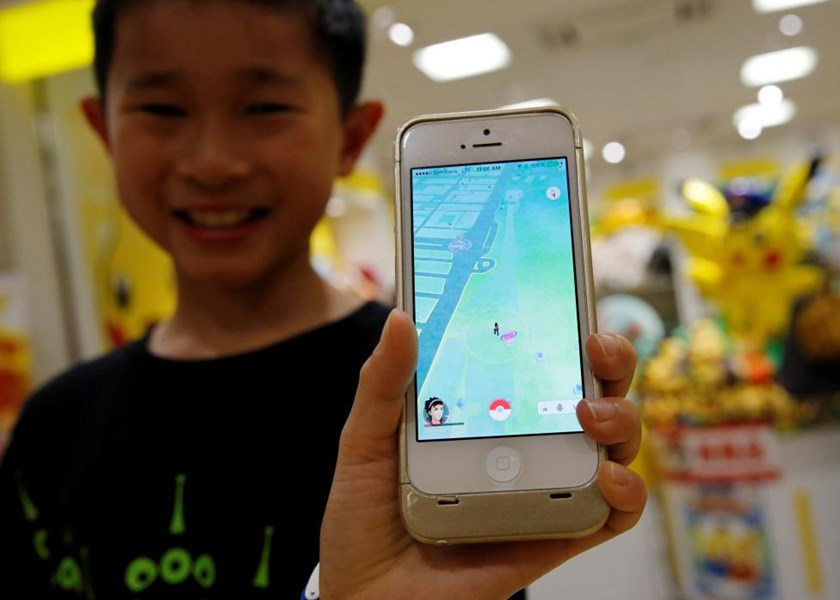A boy poses with a mobile phone displaying the augmented reality mobile game 'Pokemon Go' by Nintendo in front of a shop selling Pokemon goods in Tokyo, Japan July 22, 2016.
