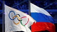 The Russian national flag (R) and the Olympic flag are seen during the closing ceremony for the 2014 Sochi Winter Olympics, Russia, February 23, 2014.