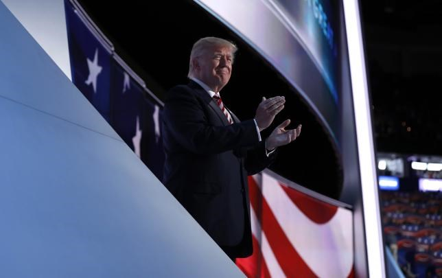 Republican U.S. presidential nominee Donald Trump applauds onstage as his running-mate Indiana Governor Mike Pence concludes his speech during the third night of the Republican National Convention in Cleveland, Ohio, U.S. July 20, 2016.