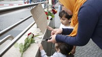 A woman lights candles on a wall near the Olympia shopping mall, where yesterday's shooting rampage started, in Munich, Germany July 23, 2016.