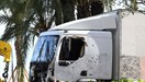 A picture taken on July 15, 2016 shows the truck, riddled with bullets, that was driven by a man through a crowd celebrating Bastille Day being towed away by breakdown lorry in the French Riviera city of Nice
