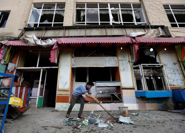 An Afghan man removes broken glass from his shop a day after a suicide attack in Kabul, Afghanistan July 24, 2016.
