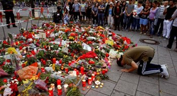 A man prays beside flowers laid in front of the Olympia shopping mall, where yesterday's shooting rampage started, in Munich, Germany July 23, 2016.
