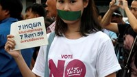 An activist of the Resistant Citizen, against the junta-backed constitution seals her mouth with duct tape and holds a placard reading ''7 Reasons To Not Accept Constitution'' during gathered to hold activities against the draft constitution, ahead of the August 7 referendum in front of the Election Commission Office in Bangkok, Thailand, June 15, 2016.