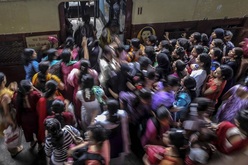 Commuters board a train at Kurla railway station during the morning rush hour in Mumbai. Photo: Bloomberg