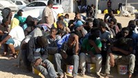 Illegal migrants sit in a port in Tagiura, east of the Libyan capital Tripoli, after 137 migrants of African origins were rescued by coast guard boats off the coast of Libya on July 21, 2016