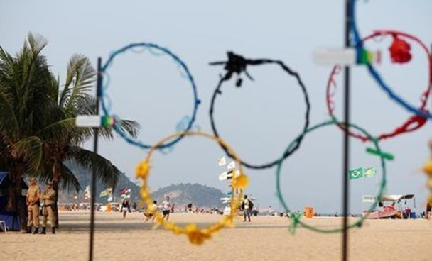 Policemen stand near mock Olympic rings made of recycled plastic in Rio de Janeiro