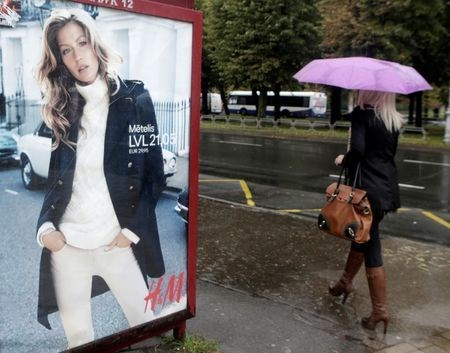 A woman walks past a H&M advertisement in Riga September 25, 2013.
