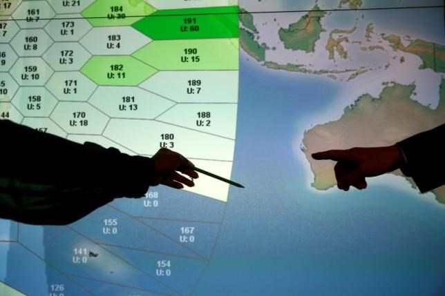Member of staff at satellite communications company Inmarsat point to a section of the screen showing the southern Indian Ocean to the west of Australia, at their headquarters in London, Britain, March 25, 2014.