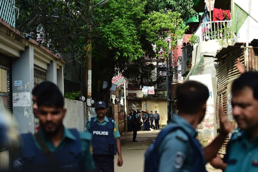 Bangladeshi police stand guard in front of the house where police killed nine suspected Islamist extremists in Dhaka on July 26, 2016