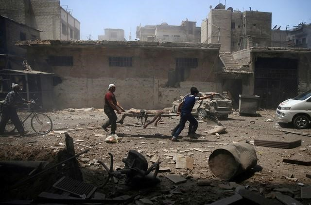 Men transport a casualty at a site hit by airstrikes in the rebel held Douma neighbourhood of Damascus, Syria, July 25, 2016.