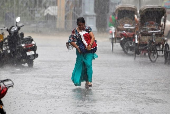 A woman walks during heavy rains in Allahabad, India, July 29, 2016.