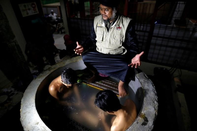 The head of a traditional drug addiction treatment center, Ustad Ahmad Ischsan Maulana, prays with two recovering drug addicts who sit immersed in a herbal bath in Purbalingga, Central Java, Indonesia July 27, 2016.
