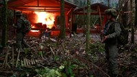 A Colombian anti-narcotics policeman stands guard after burning a cocaine lab, which police said belongs to criminal gangs, in a rural area of Calamar in Guaviare state, Colombia, August 2, 2016.