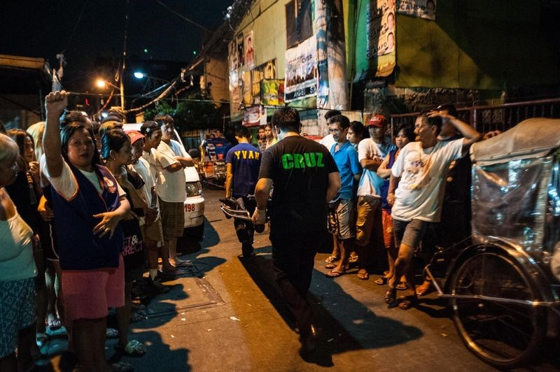 A body of an alleged drug dealer is taken out of a crime scene in Manila on July 16. Photographer: Dondi Tawatao/Getty Images