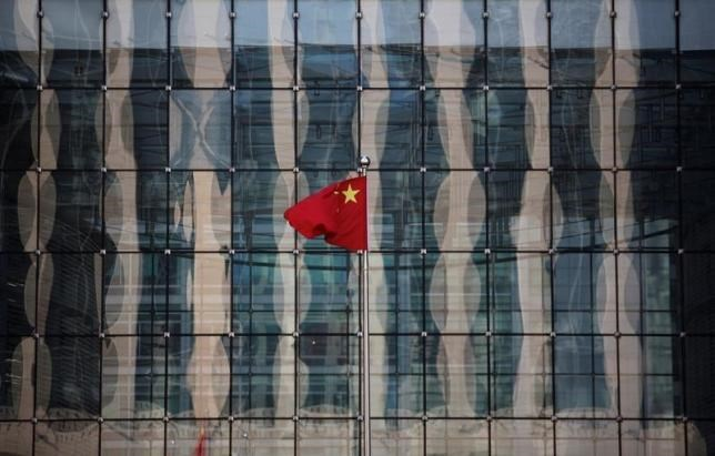 A Chinese national flag flutters at the headquarters of a commercial bank on a financial street near the headquarters of the People's Bank of China, China's central bank, in central Beijing November 24, 2014.