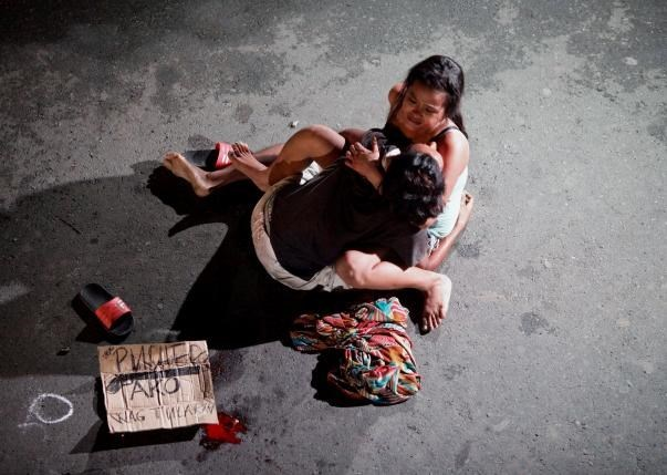 Jennelyn Olaires, 26, cradles the body of her partner, who was killed on a street by a vigilante group, according to police, in a spate of drug related killings in Pasay city, Metro Manila, Philippines July 23, 2016. Photo: Reuters/Czar Dancel