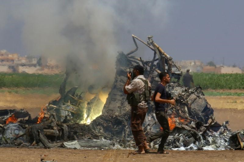 Men inspect the wreckage of a Russian helicopter that had been shot down in the north of Syria's rebel-held Idlib province, Syria August 1, 2016.