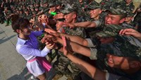 South Korean marines watch a performance by K-pop girl group 'Laboum' at a military base in Gimpo near the Demilitarized zone dividing the two Koreas on June 10, 2016