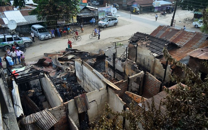 Bystanders gather near burnt-out shops following an attack on a market at Balajan Tinali, in the Kokrajhar district of India's north-eastern state of Assam, on August 6, 2016