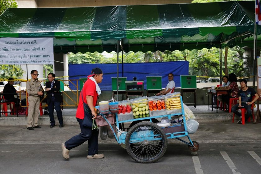 A fruit vendor pushes a cart in front of a polling station during a constitutional referendum vote in Bangkok, Thailand August 7, 2016.