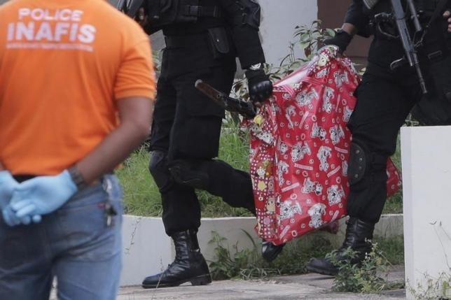 Indonesian anti-terror police carry a bag containing a suspected firearm and other evidence from a building during a raid in Batam, Riau Islands, Indonesia, August 5, 2016 in this photo taken by Antara Foto. Antara Foto/M N Kanwa/via REUTERS
