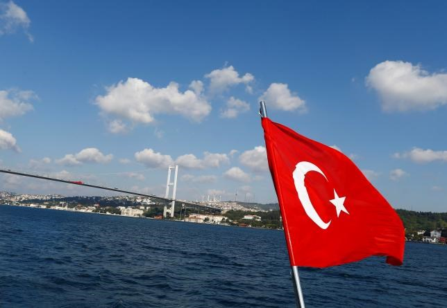 A Turkish flag is pictured on a boat with the Bosphorus bridge in the background in Istanbul, Turkey, August 6, 2016.