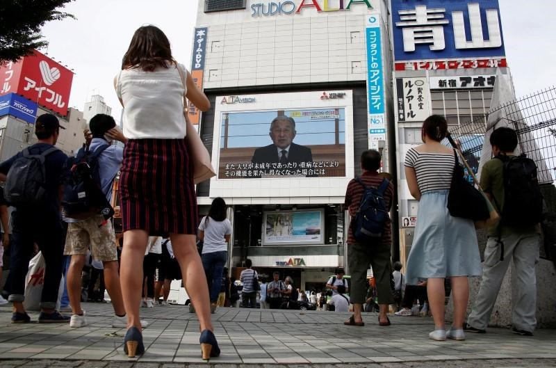 People watch a large screen showing Japanese Emperor Akihito's video address in Tokyo, Japan, August 8, 2016.
