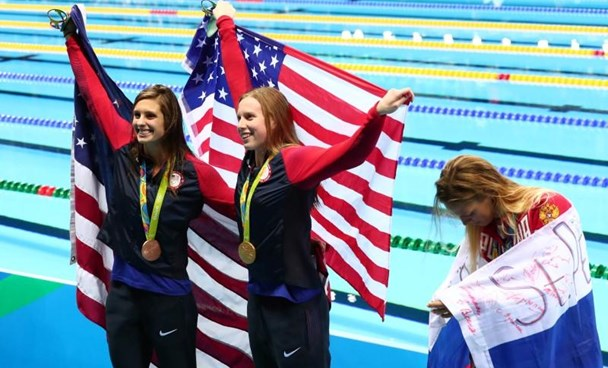 Katie Meili (USA) and Kathleen Baker (USA) hold an American flag as Yulia Efimova (RUS) reacts after the women's 100m breaststroke final during the Rio 2016 Summer Olympic Games at Olympic Aquatics Stadium. Mandatory Credit: Rob Schumacher-USA TODAY Sports