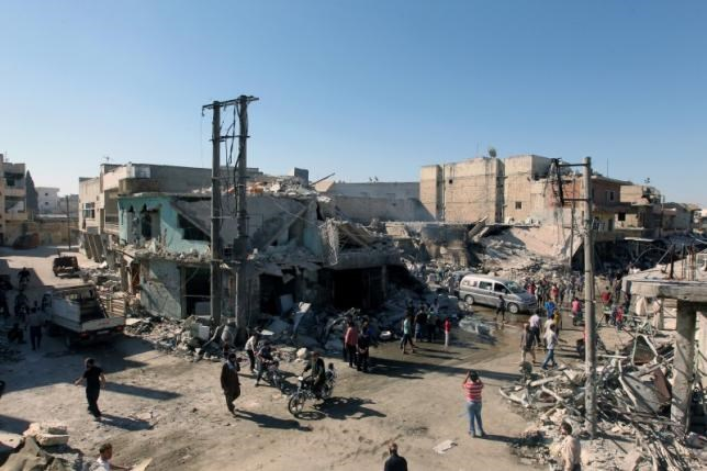 People inspect a site hit by airstrikes in the rebel held town of Atareb in Aleppo province, Syria, July 25, 2016.