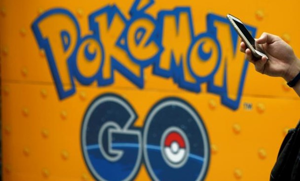 A man uses a mobile phone in front of an advertisement board bearing the image of Pokemon Go at an electronic shop in Tokyo, Japan, July 27, 2016.