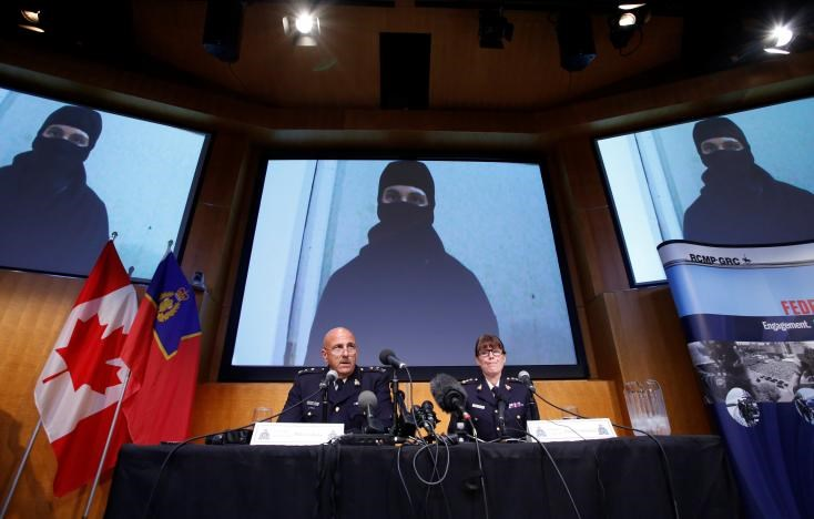 An image of Aaron Driver, a Canadian man killed by police on Wednesday who had indicated he planned to carry out an imminent rush-hour attack on a major Canadian city, is projected on screens during a news conference with Royal Canadian Mounted Police (RCMP) Deputy Commissioner Mike Cabana (L) and Assistant Commissioner Jennifer Strachan in Ottawa, Ontario, Canada, August 11, 2016.