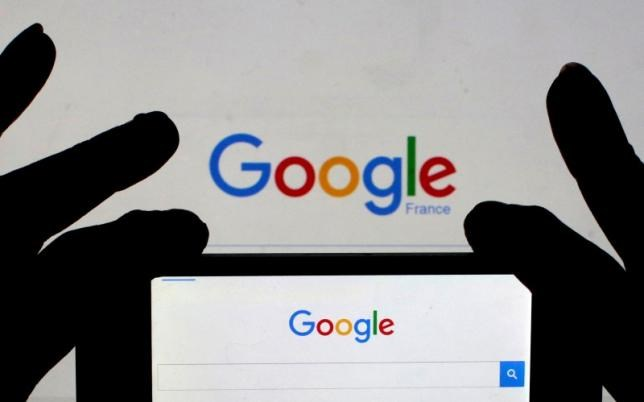 A woman holds her smart phone, which displays the Google home page, in this picture illustration taken February 24, 2016.