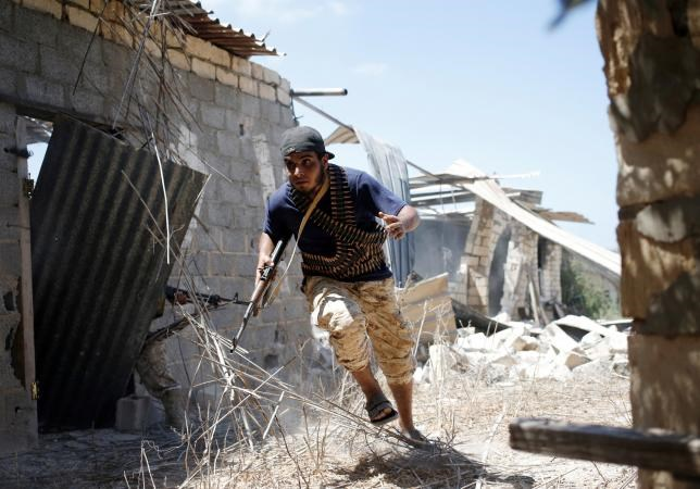 A fighter of Libyan forces allied with the U.N.-backed government runs for cover during a battle with Islamic State fighters in Sirte, Libya, July 31, 2016.