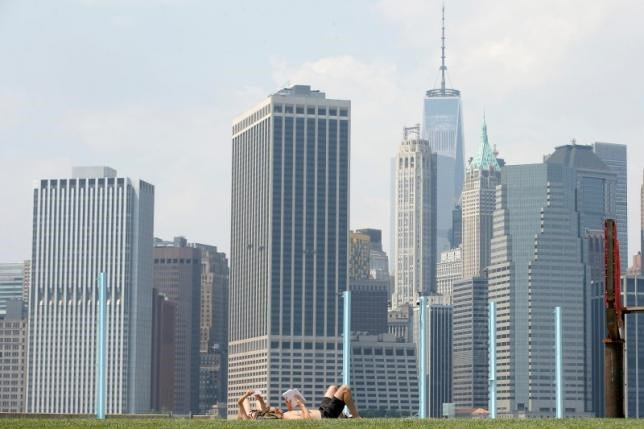 The skyline of lower Manhattan is seen as people lay on the grass in Brooklyn Bridge Park in the Brooklyn borough of New York City, U.S., May 27, 2016.