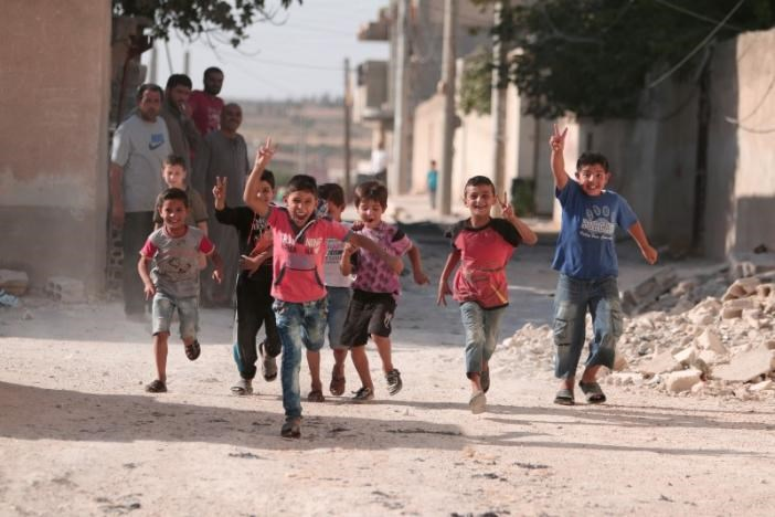 Children flash victory signs as they play in Manbij.