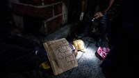 "Police inspect the body of an alleged drug dealer with his face covered with packing tape, with a cardboard sign on him reading ""I'm a pusher"" in Manila"